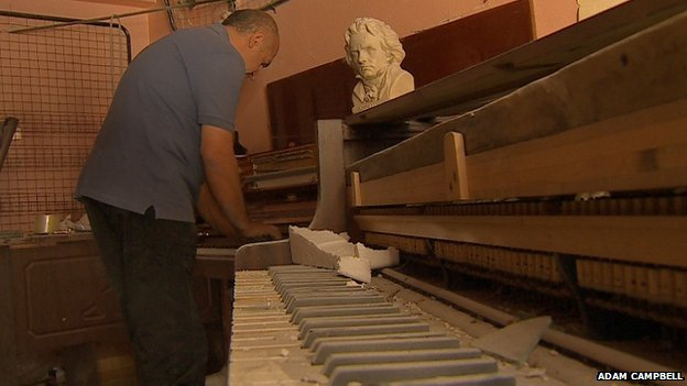 Amjad Manour by a piano at Harmony Music Shop, Homs