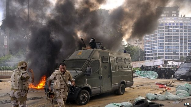 Egyptian riot police move in on a huge protest camp set up by supporters of President Morsi in Cairo (14 August 2013)