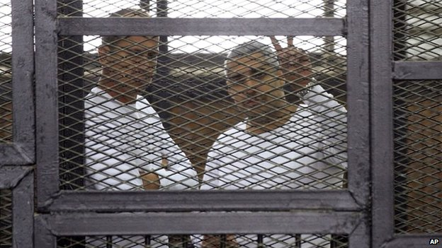 Al-Jazeera English bureau chief Mohamed Fahmy, right, and correspondent Peter Greste in a defendant's cage in a courtroom in Cairo (22 April 2014)