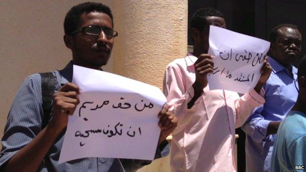 "Protesters outside the court in Khartoum hold banners saying ""Meriam has the right to be Christian"" and ""I have the right to choose any religion"" - 15 May 2014"