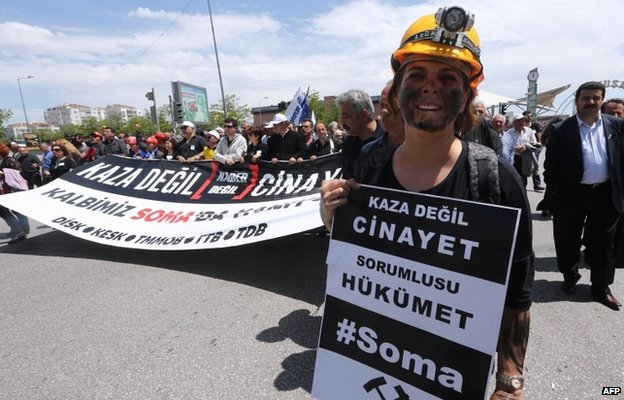 "A woman at a protest in Ankara dressed as a miner holds a sign reading: ""This is not an accident, this a murder. The government is responsible."""