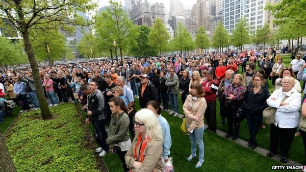 Members of the general public watch a screen projection on the World Trade Center Plaza during the dedication ceremony at the National September 11 Memorial Museum at ground zero 15 May 2014