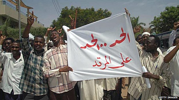 Sudanese protesters hold up a banner reading in Arabic: 'Punishment, punishment upon the apostate' during a demonstration in front of a criminal court in Khartoum in May 2005
