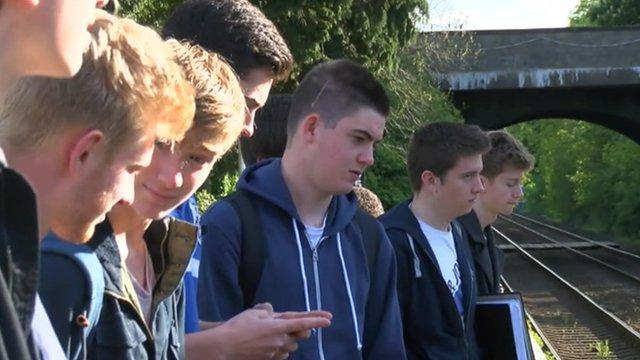 Teenage boys wait for a train