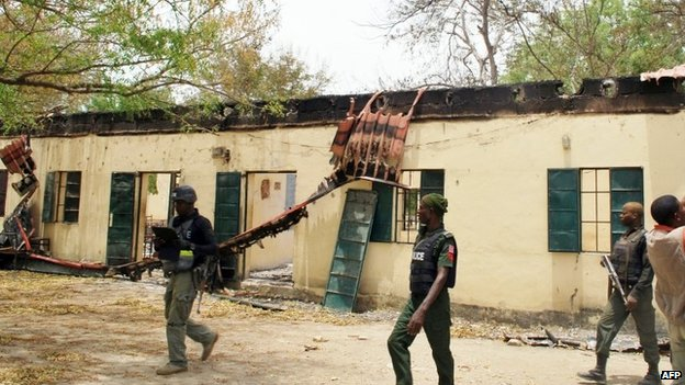 Nigerian policemen walk past Government Girls Secondary School in Chibok, Borno state (21 April 2014)