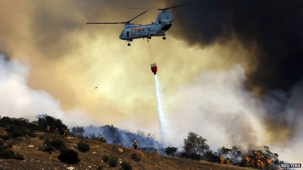 A US. military helicopter dropped water on an approaching wildfire in San Marcos, California, on 15 May 2014