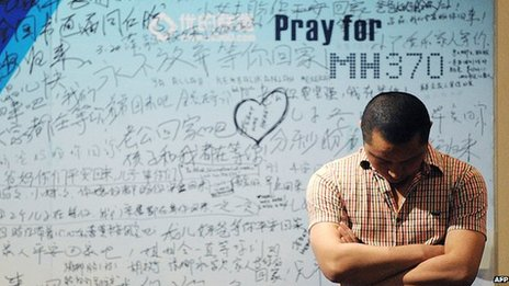 A man stands at a memorial wall for MH370