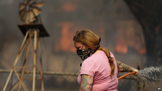 A woman uses water on a fire in Escondido, California, on 15 May 2014