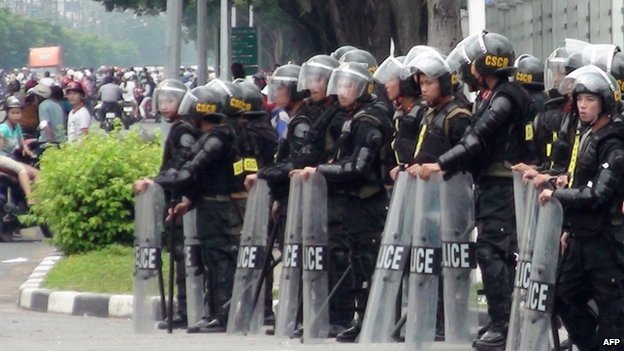 Riot police stand guard on a street outside a factory building in Binh Duong on 14 May 2014, as anti-China protesters set more than a dozen factories on fire in Vietnam