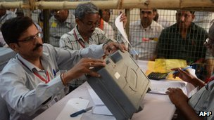 Indian election officials open an Electronic Voting Machine (EVM) at a counting centre in New Delhi on May 16, 2014.