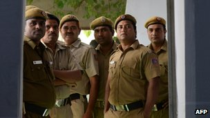 Policemen look on as results are announced at a Delhi voting centre