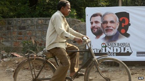 An Indian cyclist rides past a hoarding featuring images of Bharatiya Janata Party (BJP) prime-ministerial election candidate Narendra Modi and Congress Party prime-ministerial candidate Rahul Gandhi on a roadside in New Delhi