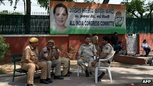 Indian police personnel sit outside Congress Party headquarters in New Delhi on May 16, 2014.