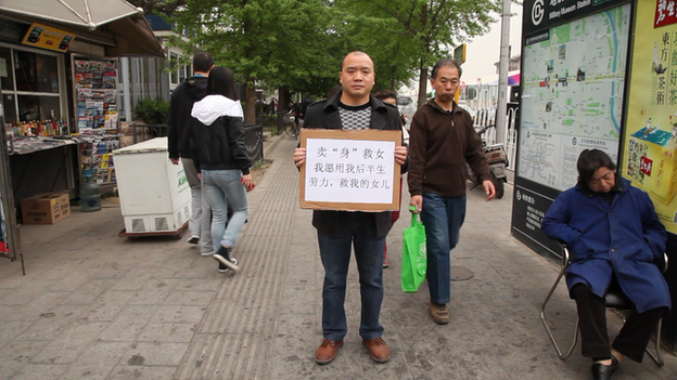 "Cheng Bangjian stands in a Beijing street and holds a sign which reads: ""I will work the rest of my life for anyone who funds my daughter's medical care."""
