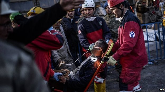 Rescuers evacuate a colleague after inhaling smoke at a mine in Soma, Turkey, on 15 May 2014