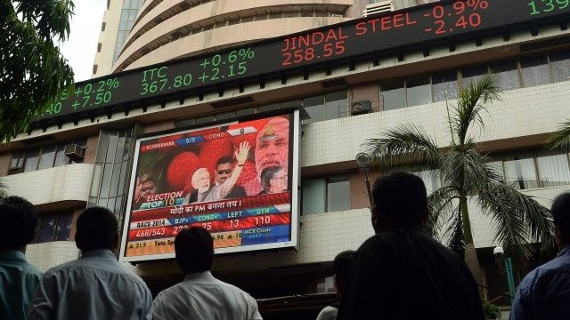 Indian pedestrians watch as a digital broadcast presents the rolling share price information