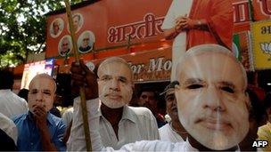 Bharatiya Janata party (BJP) workers wear masks of BJP prime ministeral candidate Narendra Modi as they celebrate outside the party office in Mumbai on 16 May 2014