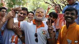 A supporter of India's main opposition Bharatiya Janata Party (BJP) wears a mask of party leader and India's next prime minister Narendra Modi as he celebrates with others preliminary results that show the BJP winning by a landslide, in Bangalore, India, Friday, 16 May 2014