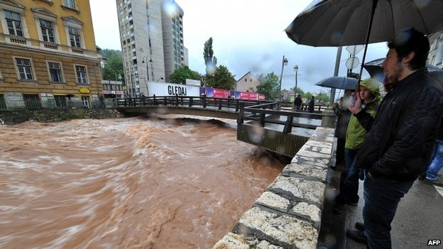 Residents of Sarajevo look at the river Miljacka on 14 May 2014