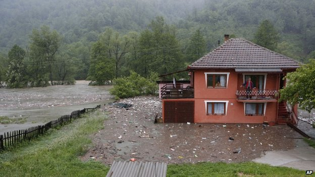 A Bosnian man looks out from a balcony at floodwaters surrounding his house in the village of Topcic Polje, near the central Bosnian town of Zenica, on 15 May 2014.