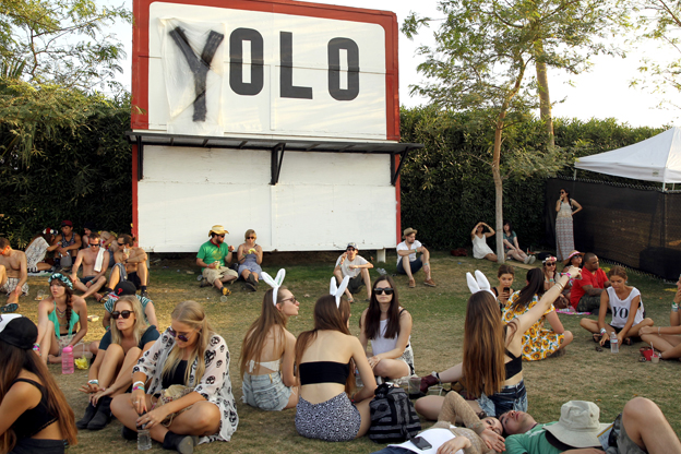 "Crowds at Coachella festival 2014 sit near a sign modified to say ""Yolo"""