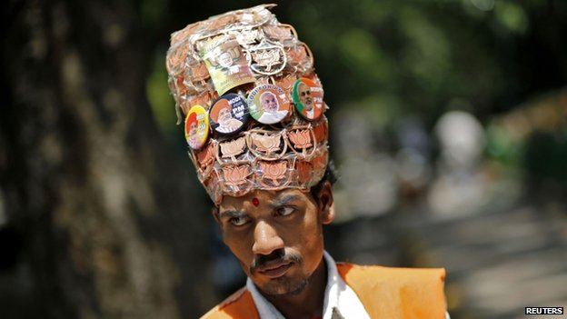 A supporter of the BJP wears headgear with badges of louts, the election symbol of the BJP