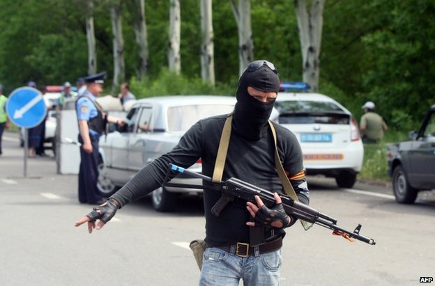 A pro-Russian militant mans a checkpoint along with a police officer near Donetsk, 15 May