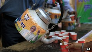 A man pours tea from a kettle with a portrait of Bharatiya Janata Party (BJP) leader and India's next prime minister Narendra Modi, outside the BJP party office in New Delhi, Friday, 16 May 2014