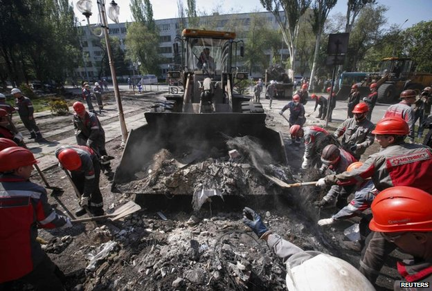 Workers clear away debris in Mariupol, eastern Ukraine, 16 May