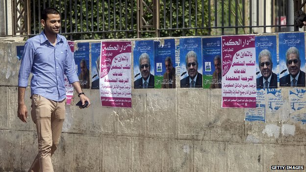 Man walks past election campaign posters