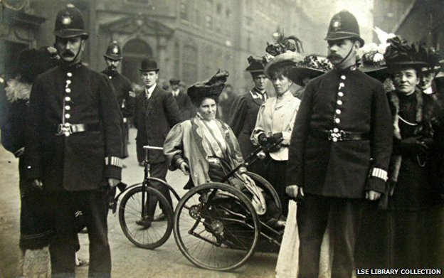 Rosa May Billinghurst in her 'invalid tricycle' surrounded by people