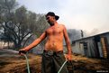 Glenn Farrell (front) helps his brother Joe Brown as they douse water on smouldering vegetation around their home during a wildfire  in Escondido, California