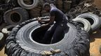 A Sudanese man cuts a heavy duty machine tyre into rubber pieces in Omdurman, Sudan on 12 May 2014