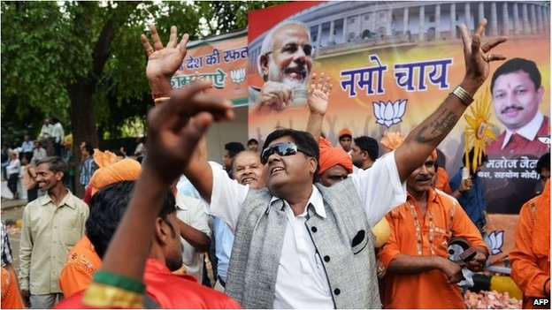 BJP supporters dance in front of the party headquarters in New Delhi
