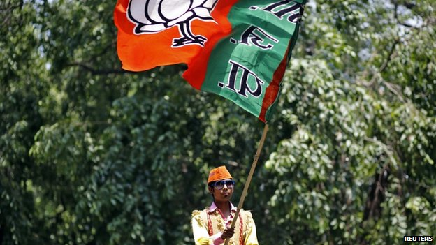 A supporter of the BJP waves the party flag during celebrations after learning of initial poll results outside the party headquarters in New Delhi May 16, 2014.