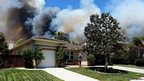 A man talks on a phone as a wildfire is seen approaching the neighbourhood in Carlsbad, California