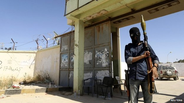 A rebel fighter holds a rocket propelled grenade launcher outside the militia camp attacked in Benghazi - 16 May 2014