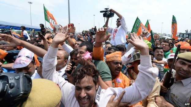 Supporters greet an unseen Narendra Modi as he arrives at Indira Gandhi International Airport in New Delhi on 17 May 2014
