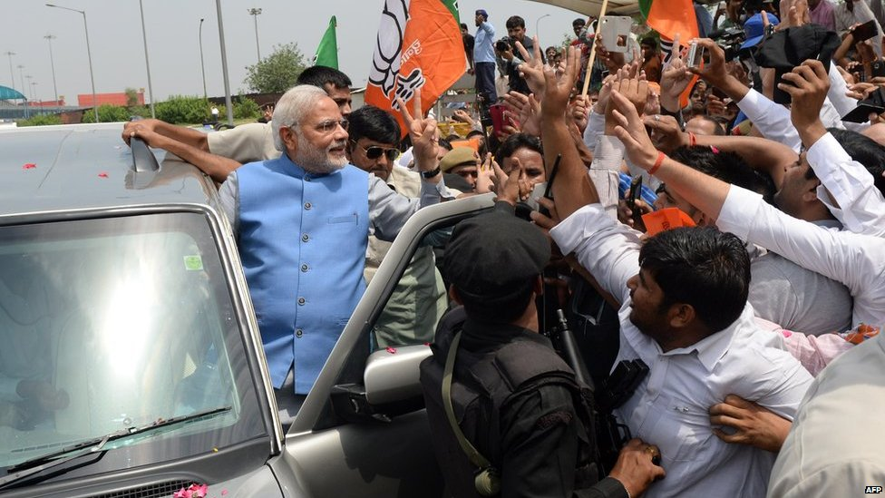 Chief Minister of the western Indian state of Gujarat and Bharatiya Janata Party (BJP) prime-ministerial candidate Narendra Modi waves to supporters as he arrives at Indira Gandhi International Airport in New Delhi on 17 May 2014