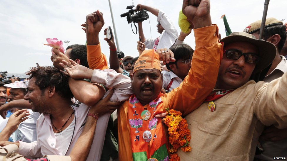 Supporters of Hindu nationalist Narendra Modi, prime ministerial candidate for India's main opposition Bharatiya Janata Party (BJP), cheer as Modi arrives at the airport in New Delhi, 17 May 2014