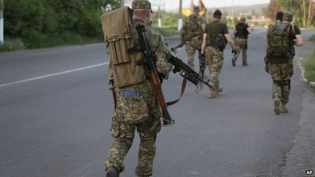 Pro-Russian militants walk to their positions to fight against Ukrainian government troops outside Sloviansk, eastern Ukraine, 17 May