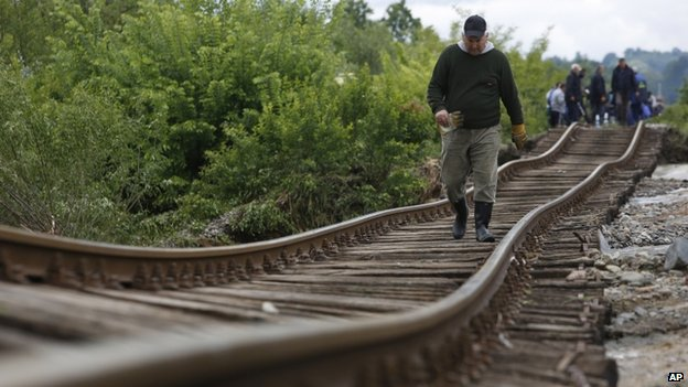A Bosnian man walks on a damaged railway track near Tuzla 140km (87 miles) north of Sarajevo, Bosnia (17 May 2014)