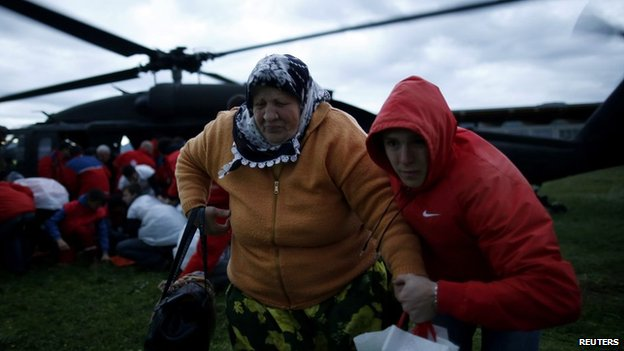 A woman and her son move away from an European Union Force (EUFOR) helicopter after being rescued from the flooded Serici village near Zepce in Bosnia on 17 May 2014