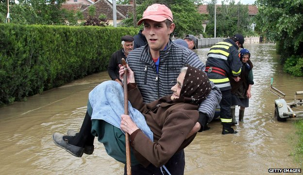 A Serbian rescuer carries an elderly woman in the village of Obrez, south of Belgrade, on 17 May 2014.