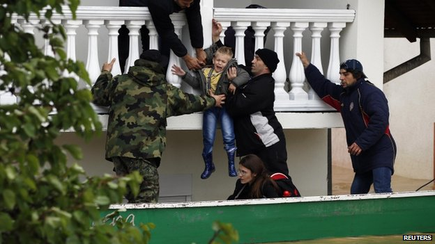 Serbian army soldiers moves a boy from a flooded house in the town of Obrenovac on 17 May 2014