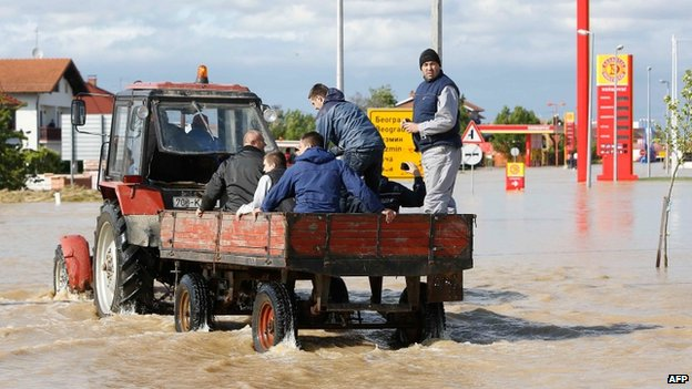 Bosnian men ride a tractor in a flooded street in the eastern-Bosnian town of Bijeljina on 17 May 2014