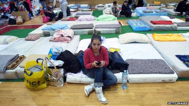 A girl sits on a mattress at a evacuation centre in Belgrade on 17 May 2014