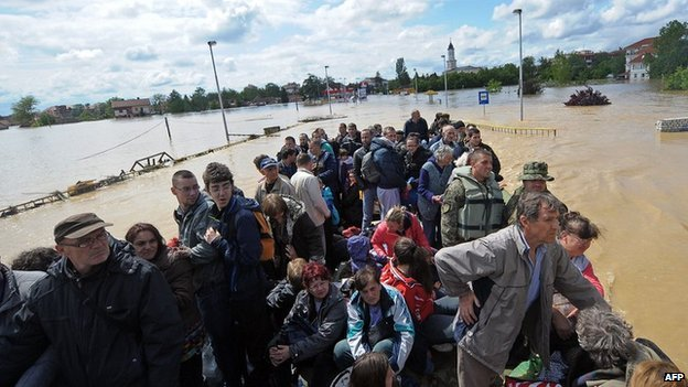 A group is evacuated by an amphibious vehicle over flooded streets in the town of Obrenovac, near Belgrade, on 17 May 2014.