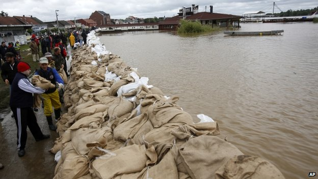 People build a dam made up of sandbags by the bank of the Sava river in Sremska Mitrovica, Serbia, on 17 May 2014