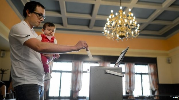 A man casts his ballot on May 18, 2014 in Bulle, western Switzerland, during a referendum on minimum wage